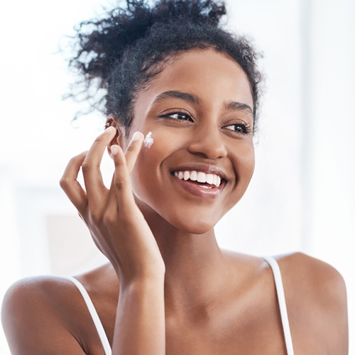 Lady applying cream to face